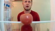 Young man opens the fridge want to eat but finds only one tomato and desparately takes and eats it video