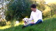 young man petting white labrador dog video