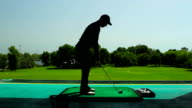 Young man playing golf in the shadow video