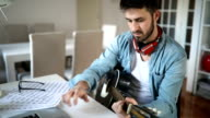 Young man playing guitar at home video