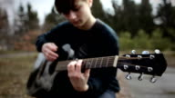 Young man playing guitar in park video