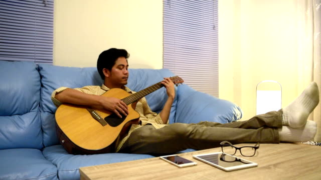 Young man playing guitar relax after time out video