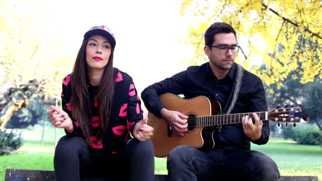 Young man playing guitar while beautiful woman sitting next to him video