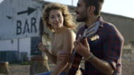 Young man playing guitar with woman video