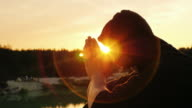 Young man praying at sunset. He sits in profile to the camera hood, clasped his hands together in prayer video
