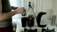 A young man putting ground coffee from a mill into a pot and pouring water. video