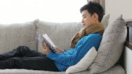 Young man reading a book on sofa and relax at home video