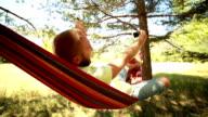 Young man relaxing on hammock taking selfie video