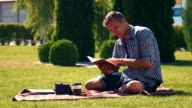 Young man relaxing reading a book video