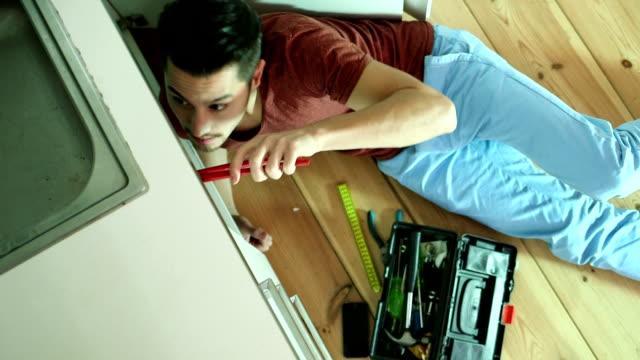 Young man repairing sink video