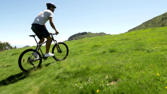 Young man ride along by mountain-bike in outdoor nature mountain scenery in summer day - gimbal steadicam HD video footage video
