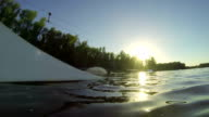 Young man rides a wakeboard next to the camera. Splashes in the  camera in Slow Motion. video