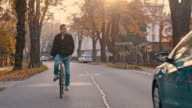 SLO MO Young man riding a bicycle along treelined road video