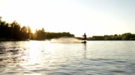 A young man riding a wakeboard at sunset video