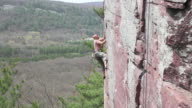 Young man rock climbing video