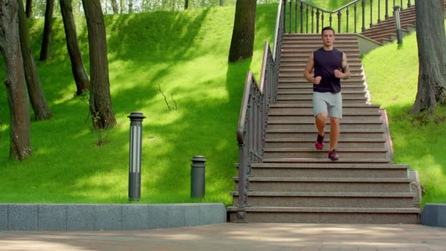 Young man running down stairs in slow motion. Healthy lifestyle concept video