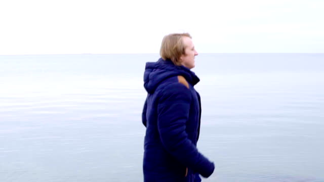 Young man running in beautiful nature landscape by the sea in coat video