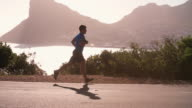 Young man running on an empty coastal road, slow motion video