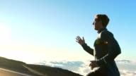 Young Man Running on Mountain Road at Sunset Above the Clouds. Slow Motion HD video