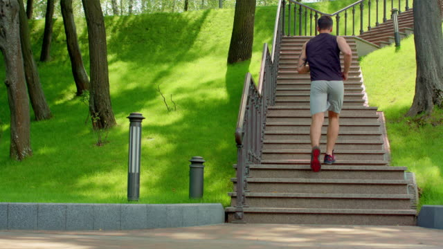 Young man running upstairs in slow motion. Young man running up stairs at park video