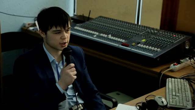 Young man says with a microphone, against background of a mixing console video
