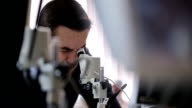 Young man screws up his eyes to look object into microscope video