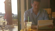 Young man searching something in tablet drinking iced tea from tubule video