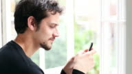 Young man sending an SMS on his mobile phone video