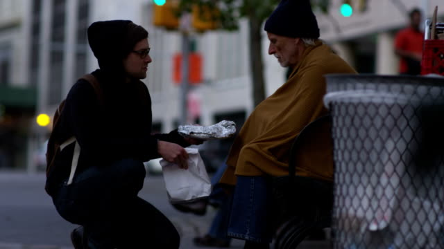 Young man shares food with homeless person video
