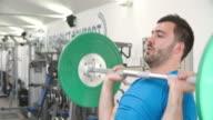 Young man shoulder pressing barbells at a gym video