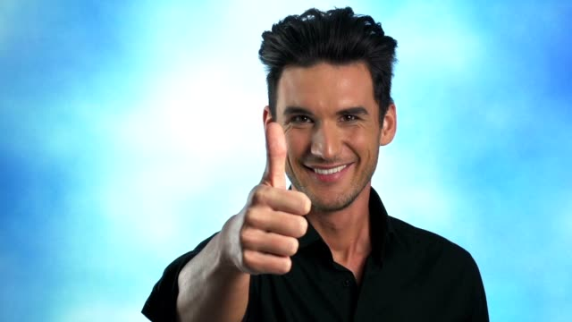 Young man showing thumbs up to camera video