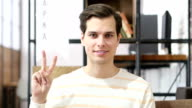 Young man showing victory sign , success in investment video