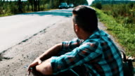 young man sit at road in countryside. Hitchhiking. Waiting. Smoking cigarette video