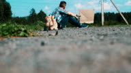 Young man sit at road in countryside with cardboard plate. Hitchhiking. Problem video