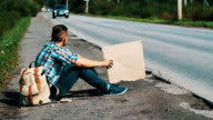 Young man sit at road in countryside with cardboard plate in hands. Hitchhiking video