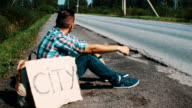 Young man sit at road in countryside with thumb up. Hitchhiking. Cars. Problem video