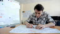 Young man sits at wooden table and creates blueprint video
