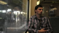 young man sits in S-Bahn in Berlin daytime in summer video