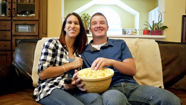 Young man sits next to girlfriend to watch television and eat popcorn video