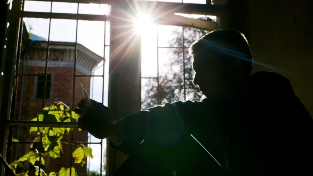 A young man sits on a windowsill in an abandoned house. Keep the syringe in his hands, on his sanctifying rays of the sun. Risk of addiction video