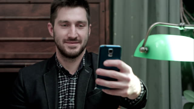 Young man sitting at the desk and taking selfie on his phone and sending it video