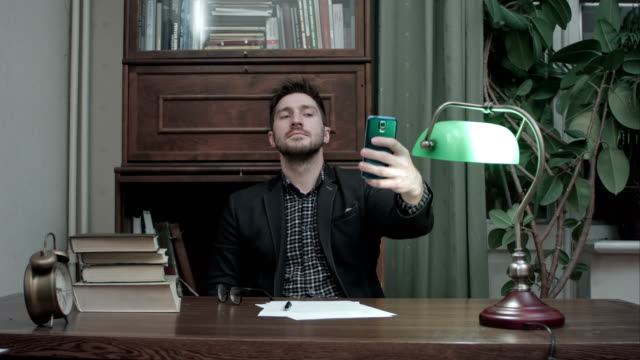 Young man sitting at the desk and taking selfies on his phone video