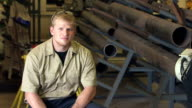 Young man sitting in factory warehouse video