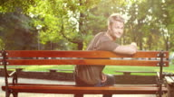 Young man sitting on park bench video