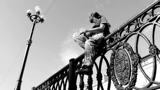 Young man sitting on the fence. Black and white video