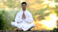 Young Man sitting on the wall and meditating video