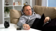 young man sleeping with laptop on the sofa at home video