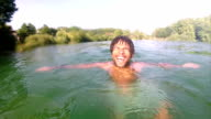 Young man smiling and shaking water off his head in river video
