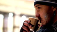 Young man smoking cigarette and drinking coffee from paper cup, video