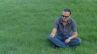 Young man smoking cigarette on the green lawn video